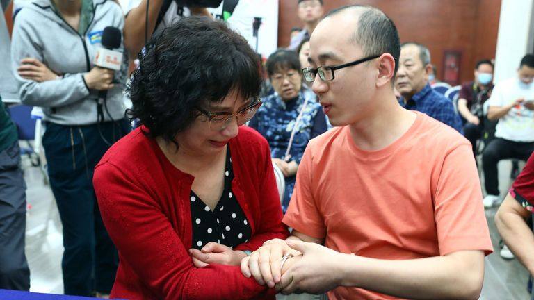 This photo taken on May 18, 2020 shows Mao Yin (R) with his mother Li Jingzhi after they were reunited in Xian, in China's northern Shaanxi province. - A Chinese man who was kidnapped as a toddler 32 years ago has been reunited with his biological parents, after police used facial recognition technology to track him down. (Photo by STR / AFP) / China OUT (Photo by STR/AFP via Getty Images)