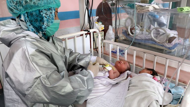 A nurse checks newborn children who lost their mothers during an attack at a hospital, in Kabul