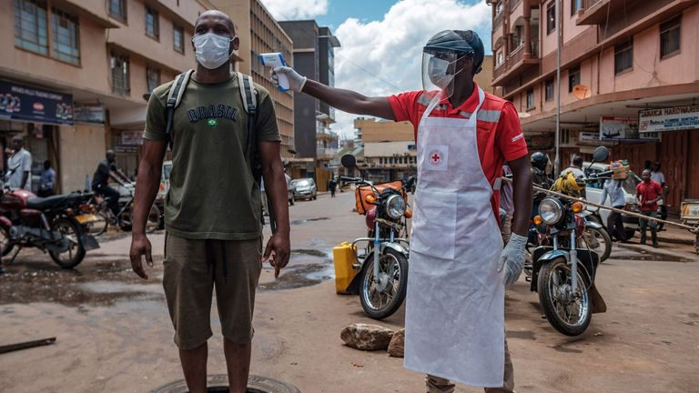 A Red Cross volunteer measures the temperature of a man before he can enter a market