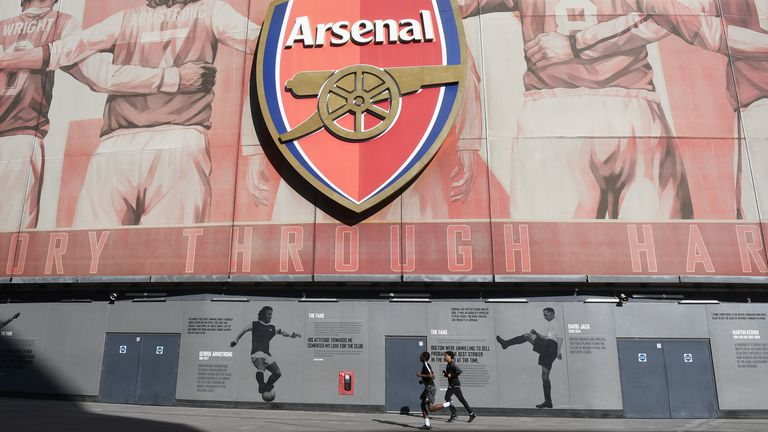 Joggers run past Arsenal's Emirates Stadium during the lockdown