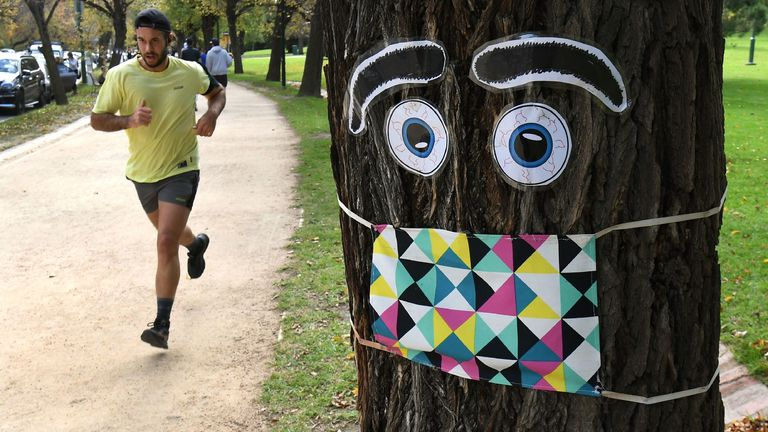 A man jogs past a giant mask and eye display stuck to a tree in Melbourne