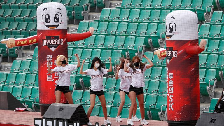 Masked cheerleaders perform for empty stands as baseball resumes in Incheon, South Korea