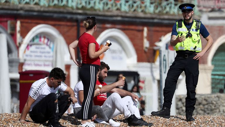 A police officer advises people to leave the beach during the warm weather in Brighton
