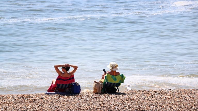 Ladies enjoy the hot weather on the beach in Brighton