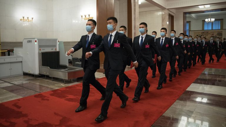 Security guards wearing face masks walk inside the Great Hall of the People