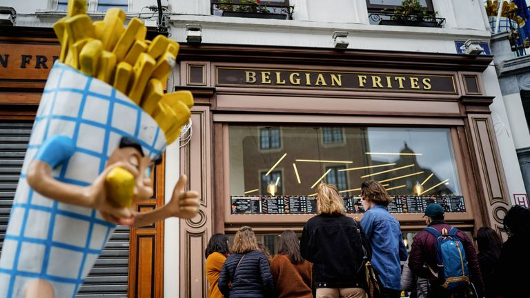People stand in line in front of a French fries vendor near the Grand Place in central Brussels