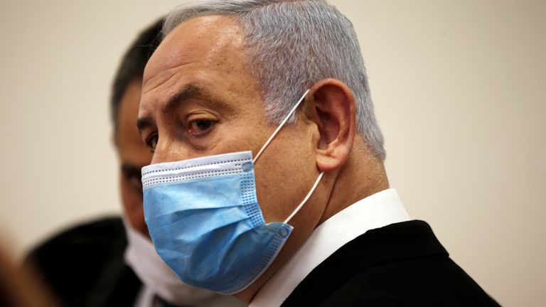 Israeli Prime Minister Benjamin Netanyahu, wearing a face mask, looks on while standing inside the court room as his corruption trial opens at the Jerusalem District Court