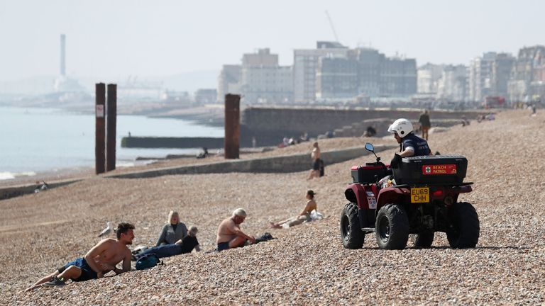 A Brighton Beach Patrol officer advises people to leave the beach