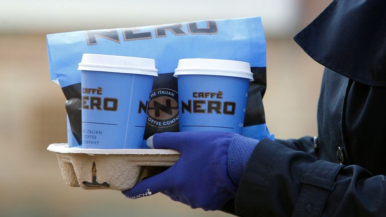 A lady walks with take away Caffe Nero cups. February 12, 2014