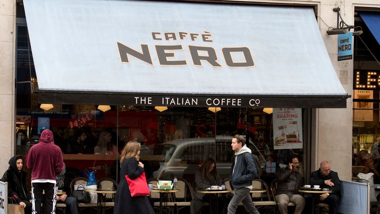 Pedestrians walk past a branch of Caffe Nero in London on November 15, 2017