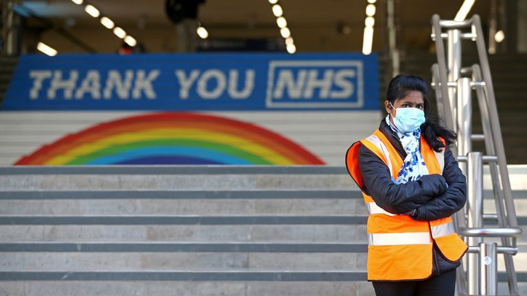 A worker wearing PPE (personal protective equipment), including a face mask as a precautionary measure against COVID-19, stands at the entrance to Cannon Street national rail station in central London on May 14, 2020