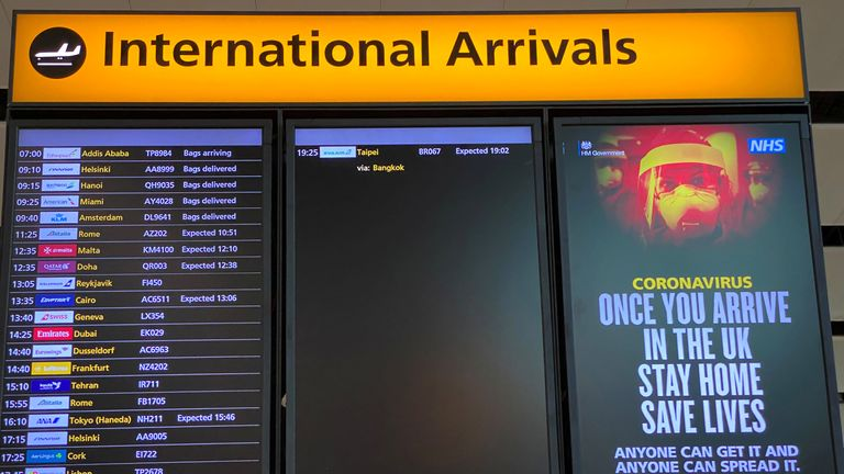 A public health campaign notice is displayed on a flight information screen at Heathrow Airport,