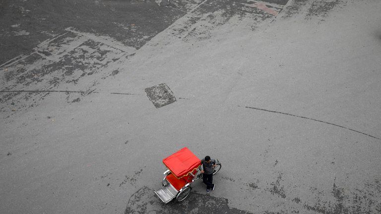 A three-wheel cycle driver waits for customers at an empty square by Hoan Kiem lake in the center of Hanoi, Vietnam March 17, 2020. REUTERS/Kham