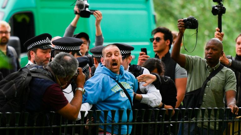A man is arrested by police as media with cameras and smartphones surround at an anti-coronavirus lockdown demonstration in Hyde Park in London on May 16, 2020, following an easing of lockdown rules in England during the novel coronavirus COVID-19 pandemic. - Fliers advertising 'mass gatherings' organised by the UK Freedom Movement to oppose the government lockdown measures and guidelines put in place to halt the spread of coronavirus in parks around the UK calling for attendees to bring a picni