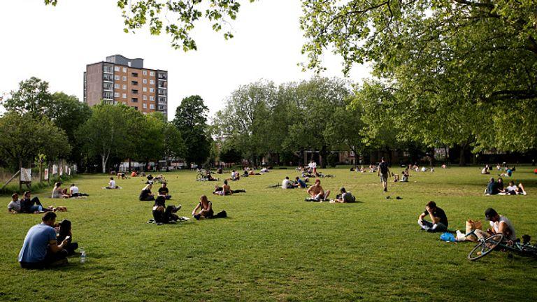People enjoy the sun in London Fields park