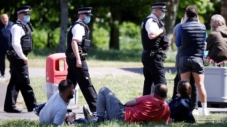 Police officers talk to a group of people who are protesting against social distancing in Newsham Park, Liverpool