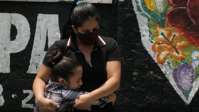 A mother comforts a child who has lost her uncle to COVID-19 in Mexico City