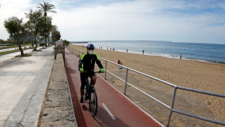 A man rides on a bicycle next to the Can Pere Antoni beach in Palma de Mallorca during the hours in which individual exercise is allowed outdoors, for the first time since the lockdown was announced, amid the coronavirus disease (COVID-19) outbreak, in Palma de Mallorca, Spain, May 2, 2020. REUTERS/Enrique Calvo