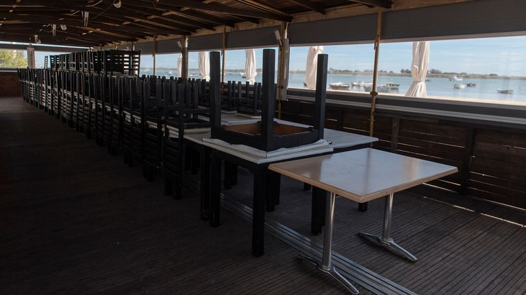 Empty chairs and tables are shown on a terrace at a beach restaurant closed due to the coronavirus lockdown in El Rompido, Spain
