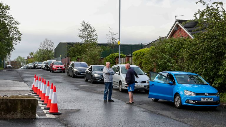 People queue in their cars outside a household waste recycling plant in Manchester which has reopened after closing in March due to the coronavirus outbreak