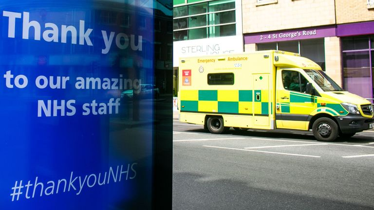 An emergency ambulance drives past a digital poster in Wimbledon thanking the NHS staff who have been caring for patients with covid-19 symptoms as the lockdown continues.