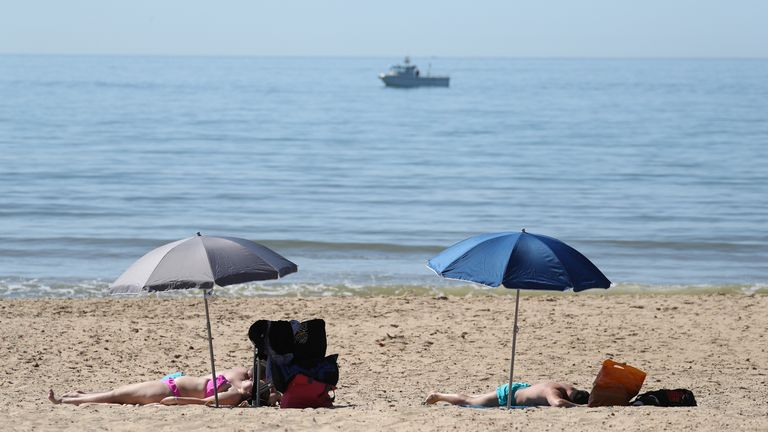 Sunbathers enjoy the hot weather on the beach by Boscombe Pier in Dorset, following the introduction of measures to bring the country out of lockdown.