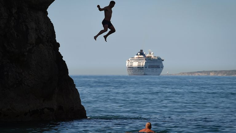 LULWORTH, ENGLAND - MAY 25: A man jumps from Durdle Door against the backdrop of a cruise ship as tourists enjoy the hot weather at Durdle Door beach on May 25, 2020 in West Lulworth, United Kingdom. The British government has started easing the lockdown it imposed two months ago to curb the spread of Covid-19, abandoning its 'stay at home' slogan in favour of a message to 'be alert', but UK countries have varied in their approaches to relaxing quarantine measures. (Photo by Finnbarr Webster/Get