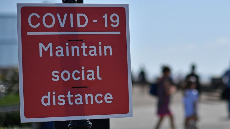 "Signs advise beachgoers arriving at the seafront to 'Maintain Social Distance due to COVID-19"", on the promenade in Southend-on-Sea, south east England on May 25, 2020, after lockdown restrictions, originally put in place due the COVID-19 pandemic, were lifted earlier this month. - British Prime Minister Boris Johnson on Sunday backed top aide Dominic Cummings despite mounting pressure from within his own party to sack him over claims he broke coronavirus lockdown regulations. (Photo by Ben STAN"