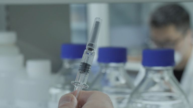 A worker holds a syringe at Beijing-based biotech company Sinovac, where work is taking place to create a coronavirus vaccine