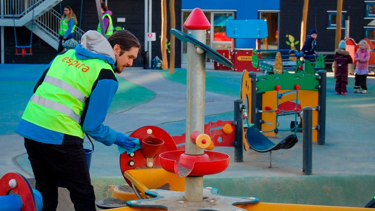 "An employee cleans a device on a playground of the ""Espira Grefsen Station Kindergarten"" in Oslo, on April 20, 2020. - Norway, which says it has the new coronavirus under control, started opening up pre-schools after a month-long closure. Authorities have said the reopening was possible because children have been less affected by COVID-19, although some parents have expressed reservations over the decision. (Photo by Pierre-Henry DESHAYES / AFP) (Photo by PIERRE-HENRY DESHAYES/AFP via Getty Imag"