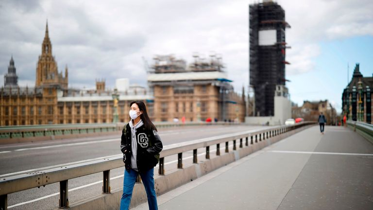 A woman walks over Westminster Bridge during lockdown.