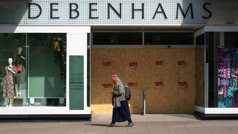 A person walks past a boarded up Debenhams, Oxford Street