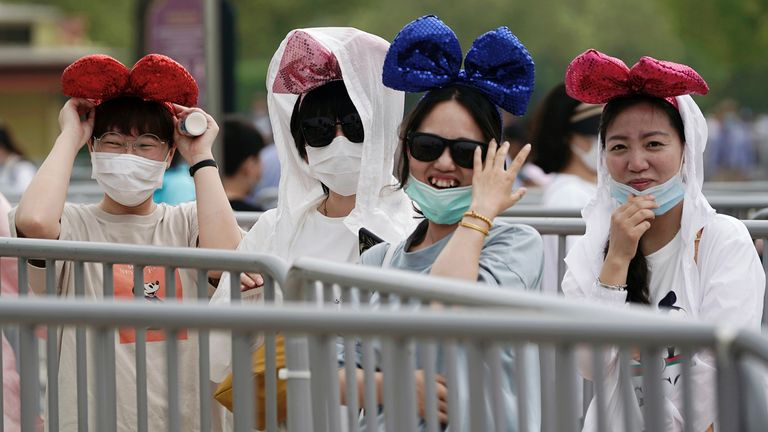 Visitors wearing face masks line up to enter the park