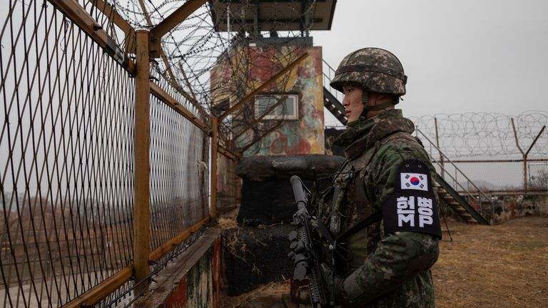 In a photo taken on December 3, 2018 a South Korean soldier stands before a security fence at a guard post inside the Demilitarized Zone (DMZ) near the Military Demarcation Line (MDL) separating North and South Korea, in South Korea's Cheorwon county