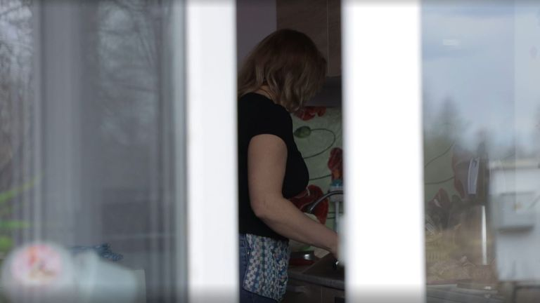 Anonymous woman seen in kitchen through glass door gap
