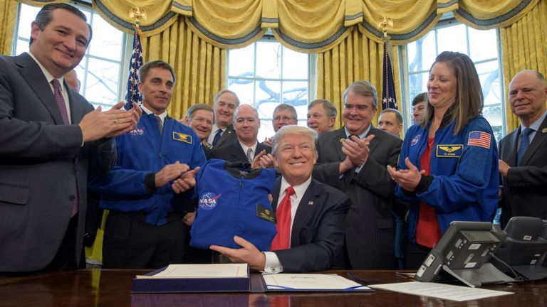 President Donald Trump, center, holds a NASA flight jacket presented to him by NASA Astronaut Office Chief Chris Cassidy, blue jacket left, after signing the NASA Transition Authorization Act of 2017, alongside members of the Senate, Congress, and National Aeronautics and Space Administration in the Oval Office of the White House in Washington, Tuesday, March 21, 2017. Also pictured, Sen. Ted Cruz, R-Texas, left, NASA Astronaut Office Chief Chris Cassidy, blue jacket left, Science Committee Chairman Rep. Lamar Smith, R-Texas, Rep. John Culberson, R-Texas, right of President, NASA Astronaut Tracy Caldwell Dyson, and others. Photo Credit: (NASA/Bill Ingalls)