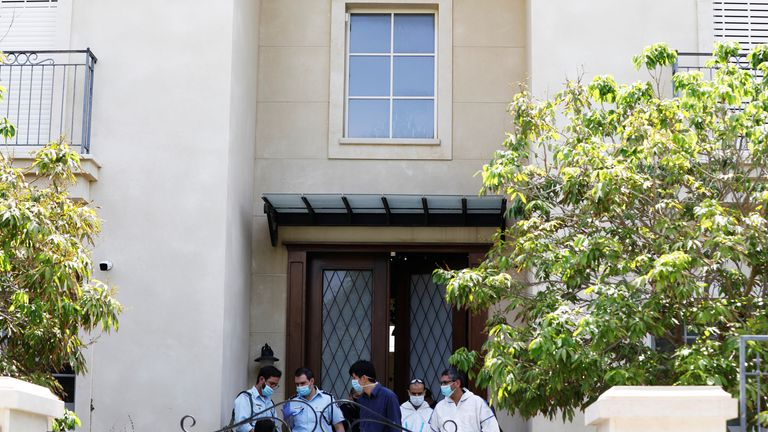 Israeli police and forensic experts are seen at the door of Du Wei's home