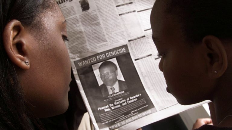 A woman and a girl look at a wanted poster of Kabuga