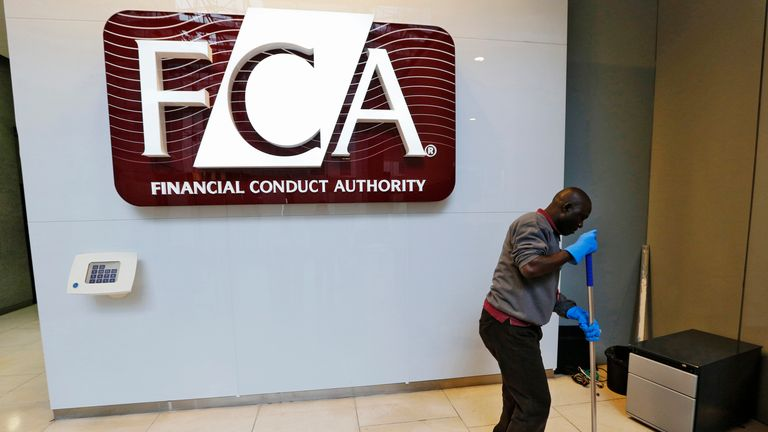A maintenance worker cleans the entrance area of the headquarters of the Financial Conduct Authority