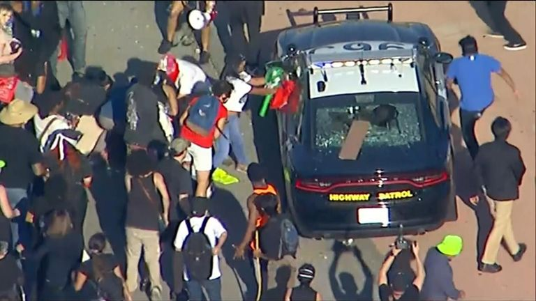 Protesters attack a California Highway patrol vehicle