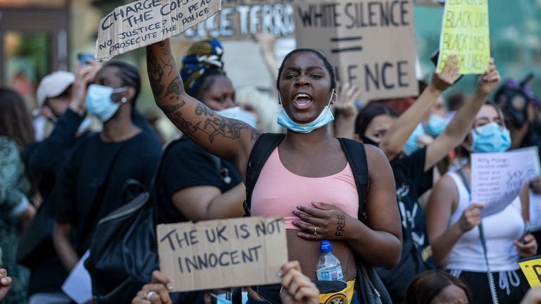 People hold placards as they join a spontaneous Black Lives Matter march through central London to protest the death of George Floyd in Minneapolis and in support of the demonstrations in North America on May 31, 2020 in London, England