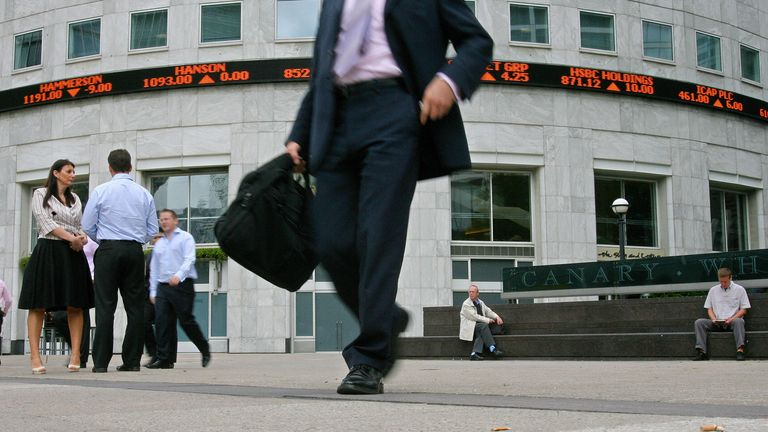 A man walks past an electronic display showing share prices in Canary Wharf business district in east London