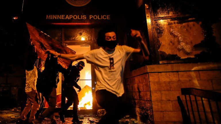 Protesters set fire to the entrance of a police station during a third night of violence