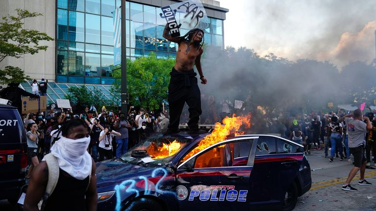 A man stands on top of a burning police car during a protest over the Minneapolis death of George Floyd while in police custody outside CNN Center on May 29, 2020 in Atlanta, Georgia. (Photo by Elijah Nouvelage/Getty Images)
