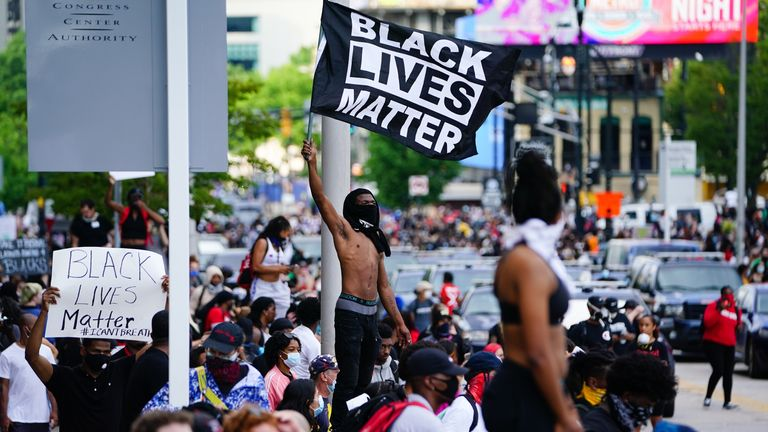 A man waves a Black Lives Matter flag during a protest over the Minneapolis death of George Floyd while in police custody outside CNN Center on May 29, 2020 in Atlanta, Georgia. (Photo by Elijah Nouvelage/Getty Images)