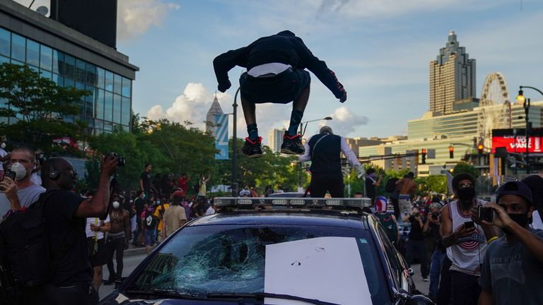 A man jumps on the roof of a police car during a protest over the Minneapolis death of George Floyd while in police custody outside CNN Center on May 29, 2020 in Atlanta, Georgia. (Photo by Elijah Nouvelage/Getty Images)