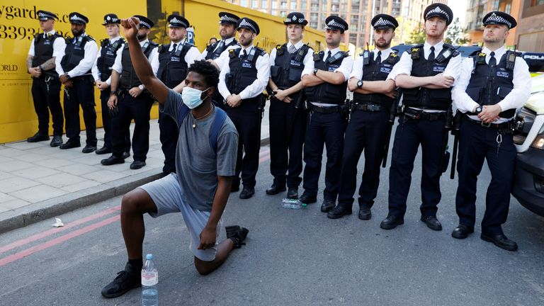 A man wearing a protective face mask kneels in front of police officers near the US Embassy, London, during the George Floyd protests