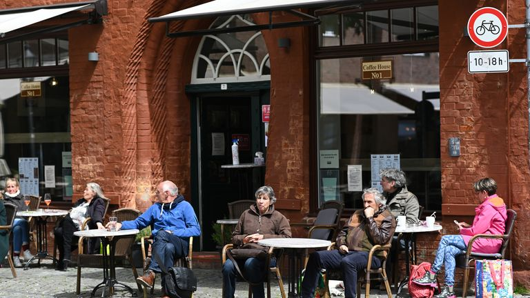 People sit outdoors at a cafe on the first day restaurants and cafes have been allowed to reopen since March