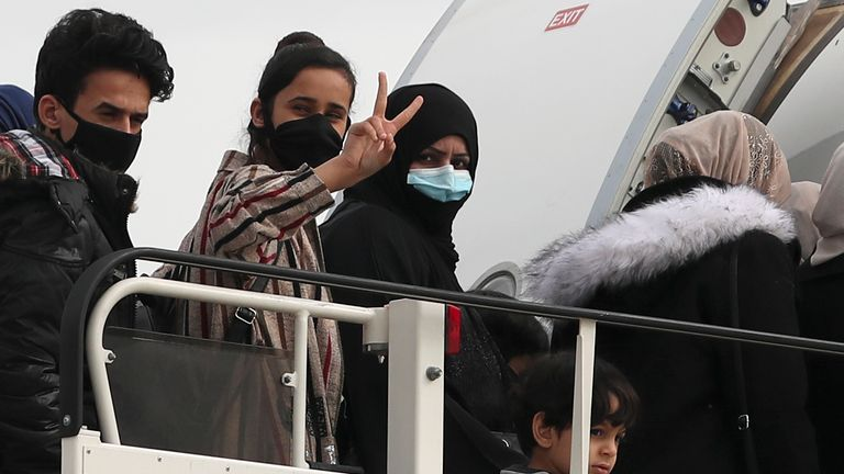 The refugees and migrants board the plane at Athens International Airport
