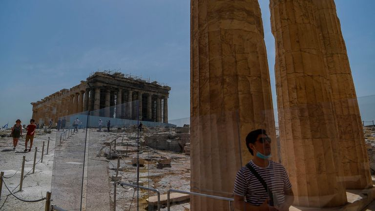 A tourist visits the Parthenon temple on the archeological site of the Acropolis in Athens, Greece